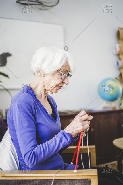 Senior woman knitting while sitting on chair in nursing home