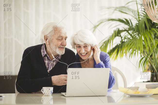 Cheerful senior couple using in-ear headphones while video calling through laptop in nursing home