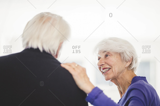 Side view of senior woman talking with man in nursing home