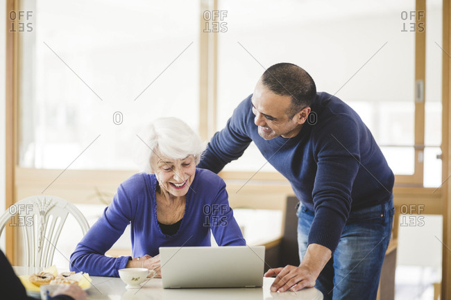 Cheerful mature man standing by mother looking at laptop on table in nursing home