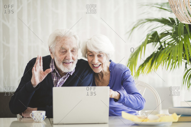 Cheerful senior couple video calling through laptop at table in nursing home