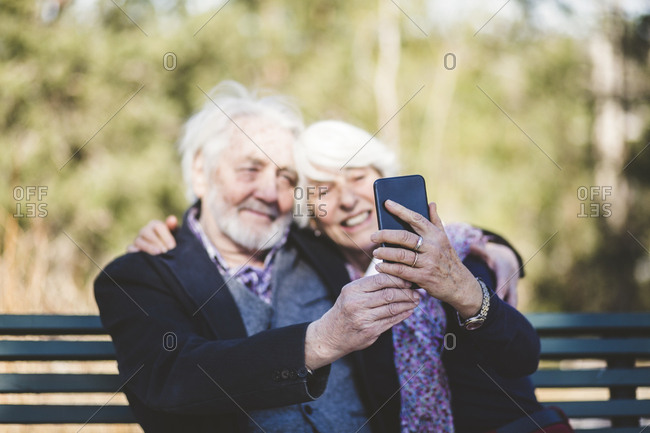 Smiling senior couple taking selfie while sitting on bench