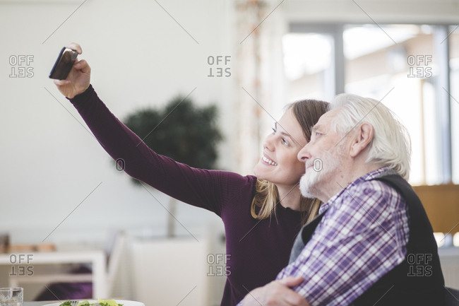 Young woman taking selfie with grandfather while sitting in nursing home