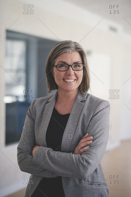 Portrait of confident mature businesswoman standing with arms crossed in office