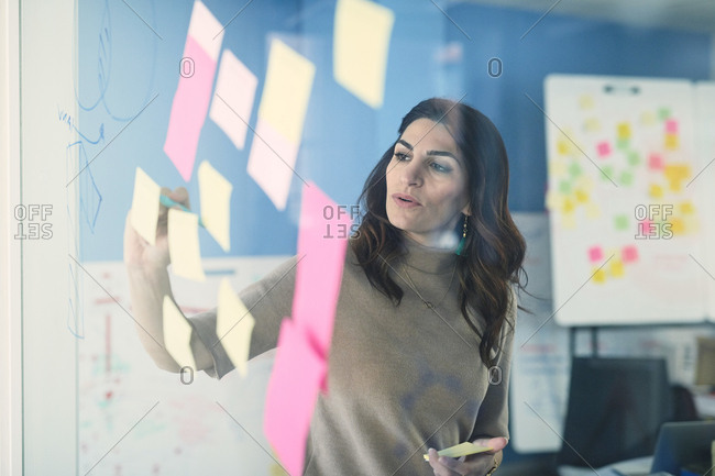 Female mature engineer writing on adhesive note stuck to glass in office