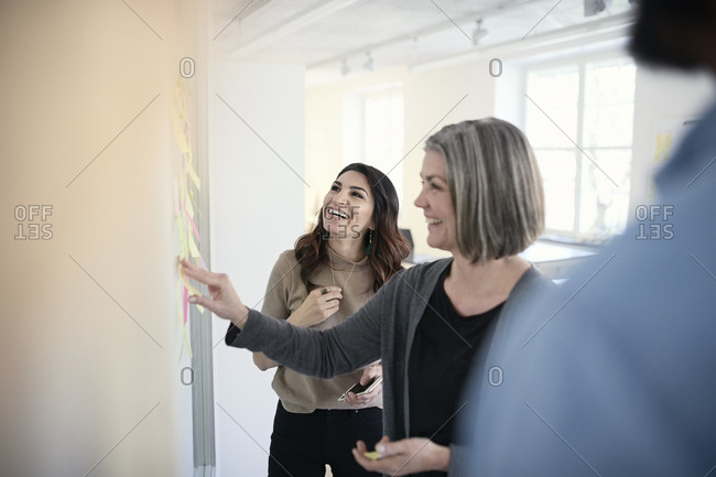 Mature female engineers smiling while reading adhesive notes stuck on glass in office