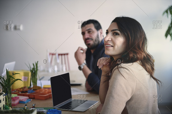 Female and male engineers looking away while sitting at table in office