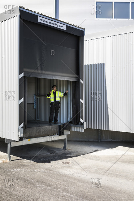 Full length of young male worker gesturing while standing on warehouse entrance