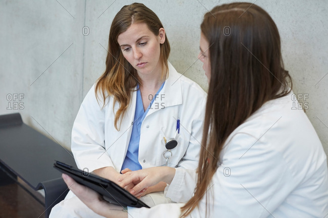 Confident young female doctor discussing with coworker over digital tablet while sitting against wall at hospital