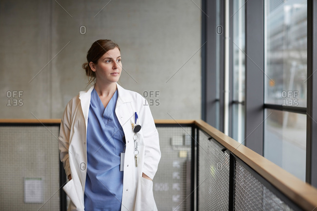 Thoughtful female doctor standing with hands in pockets while looking through window at hospital corridor