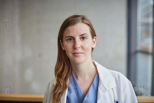 Portrait of confident mid adult female doctor standing in corridor at hospital