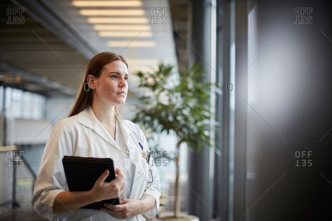 Thoughtful young female doctor with digital tablet looking through window at corridor in hospital
