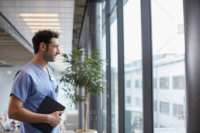 Thoughtful young male nurse while looking through window while standing at corridor in hospital
