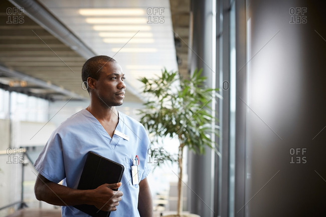 Thoughtful mid adult male nurse holding digital tablet while looking through window in corridor at hospital