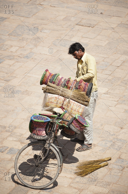 Kathmandu, Nepal - April 3, 2007: Man loading his bicycle with handmade goods