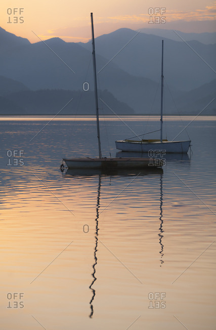Traditional fishing boats reflecting in mountain lake at sunset