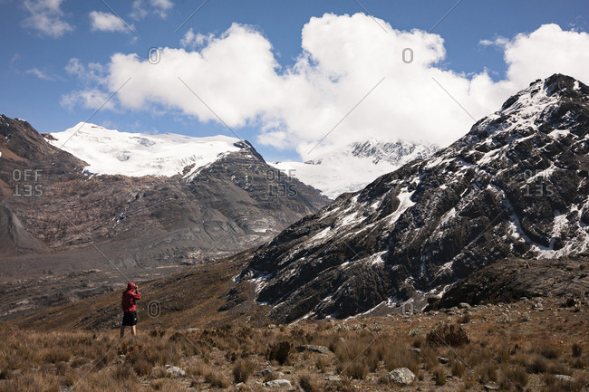 Hiker taking picture of high-altitude mountains and peaks on trail in the Andes mountains of Peru