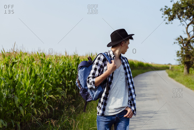 Country boy with hat and backpack walking on the country road and looking back