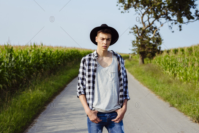 Handsome country boy with hat posing on the country road near to a cornfield