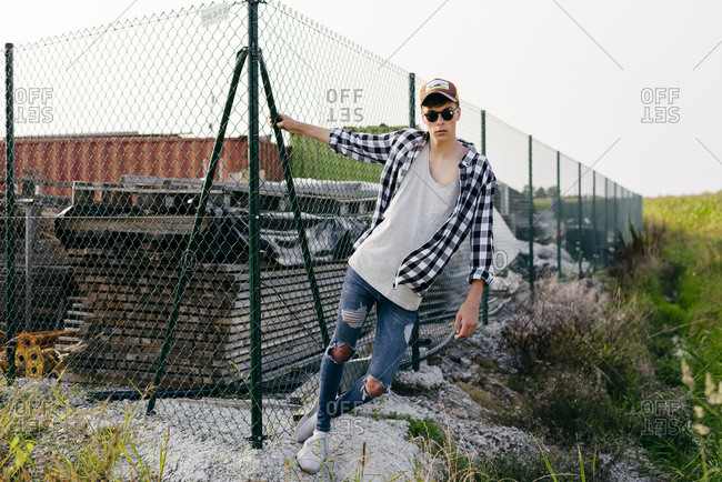 Young attractive man with sunglasses and hat clinging to the fence on the country