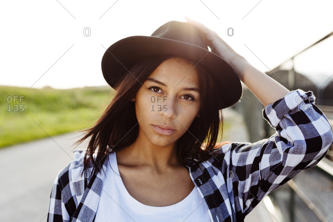 Cute black country girl holding her hat and looking at the camera