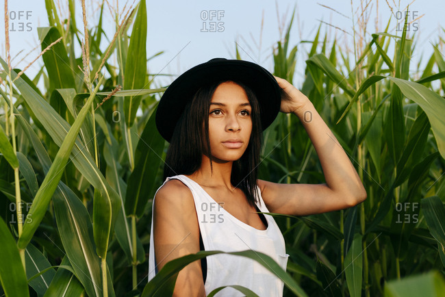 Cute black country girl with hat standing on the cornfield