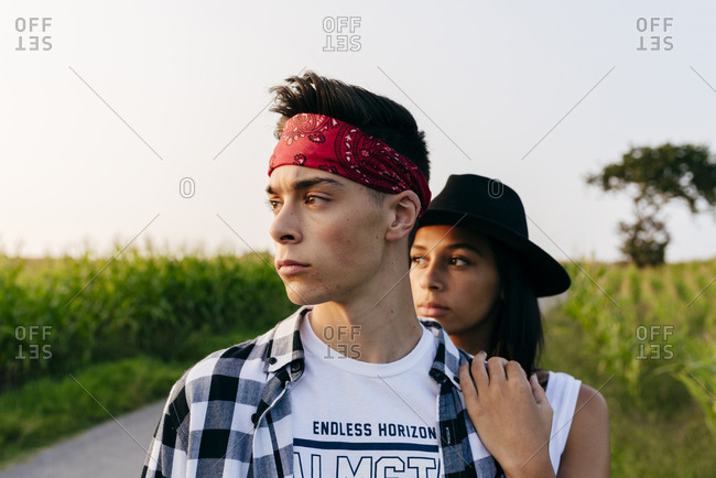 Attractive multiethnic country couple standing on the country road