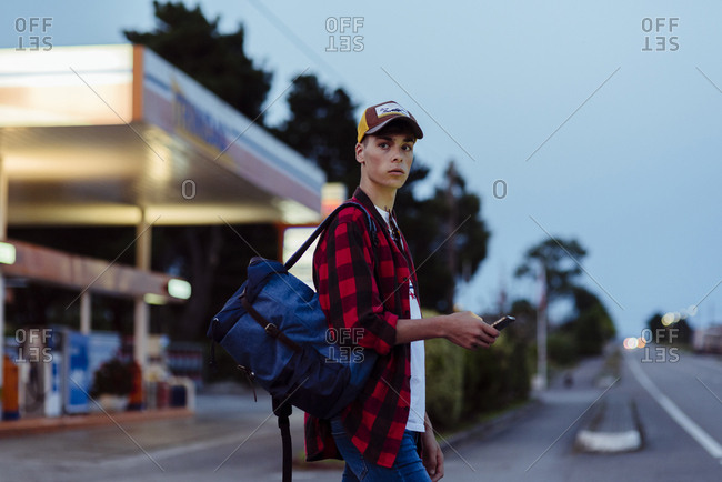 Handsome country boy with trucker cap and backpack using phone on the gas station