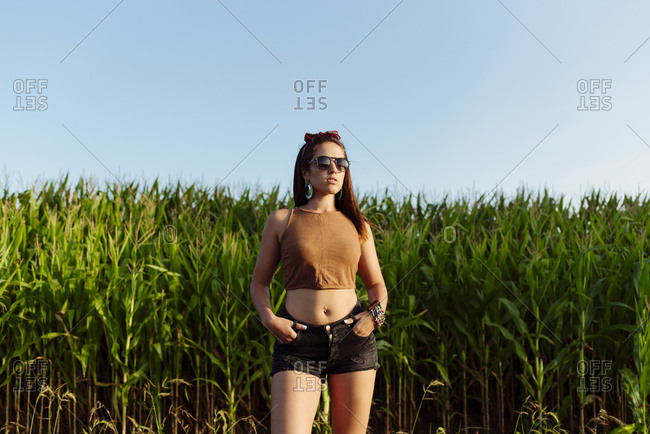 Beautiful brunette girl dressed in summer clothes with sunglasses standing near to a cornfield