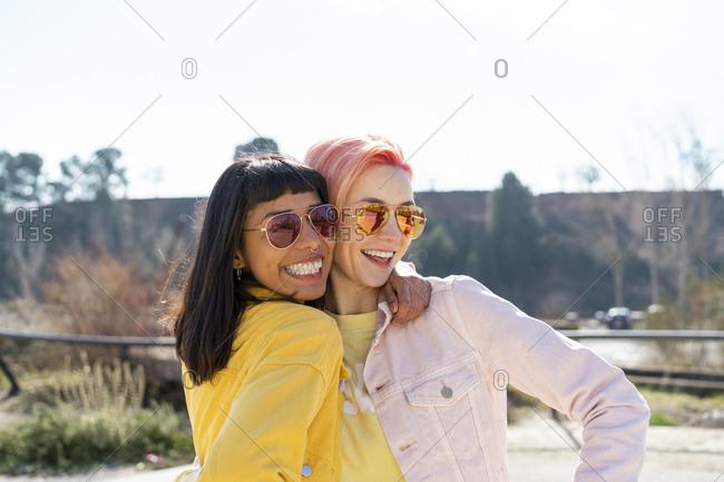 Portrait of two alternative friends embracing