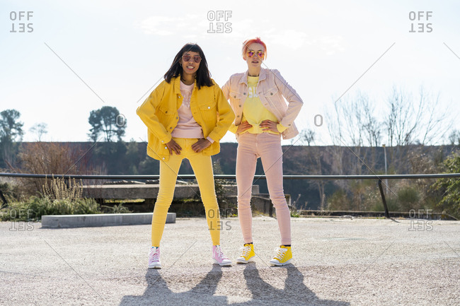 Two alternative friends wearing yellow and pink jeans clothes- posing