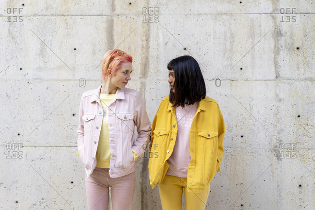 Two alternative friends having fun- wearing yellow and pink jeans clothes- face to face