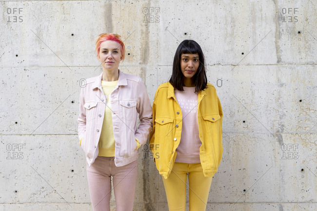 Two alternative friends having fun- wearing yellow and pink jeans clothes