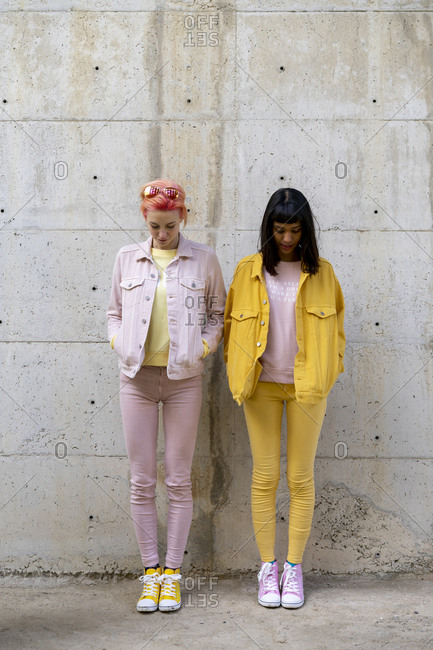 Two alternative friends having fun- wearing yellow and pink jeans clothes- looking down