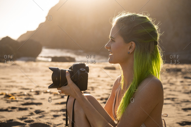 USA- California- West Coast- young woman with dyed green hair and camera sitting on the beach