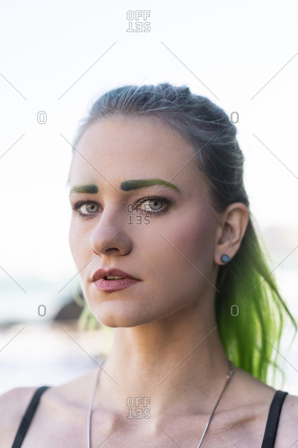 Portrait of young woman with dyed green eyebrows and hair