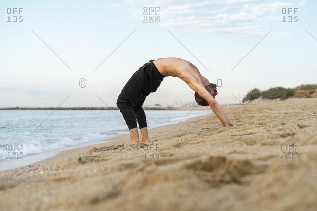 Spain, Man doing yoga on the beach in the evening- upward bow