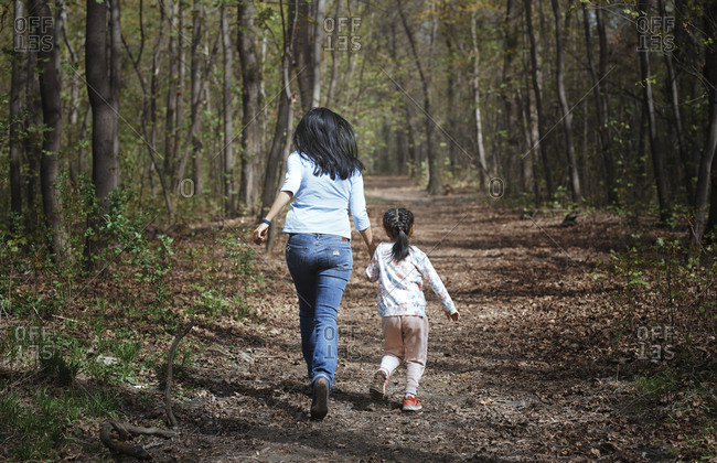 Mother and daughter running hand in hand in a park- rear view