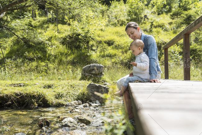 Mother and daughter sitting on wooden bridge- mountain stream