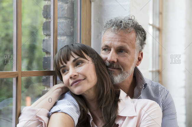 Mature couple sitting on window sill- looking out of window