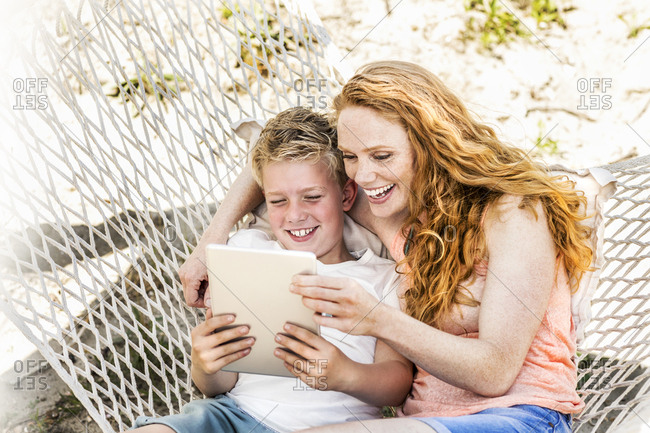 Happy mother and son in hammock looking at tablet