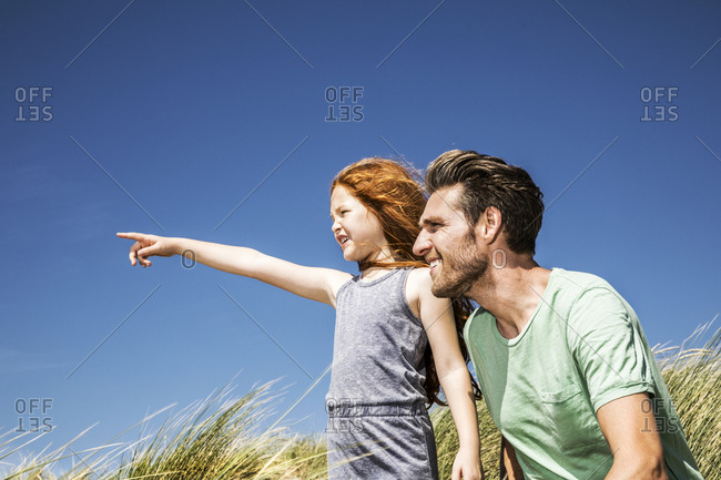 Netherlands- Zandvoort- father and daughter on in beach dunes looking out