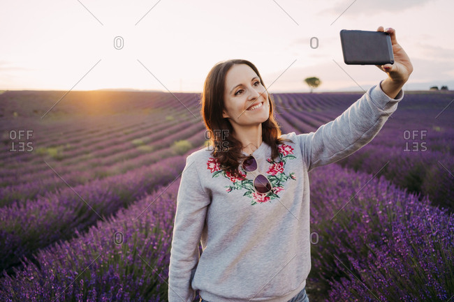 France- Valensole- portrait of smiling woman taking selfie in front of lavender field at sunset