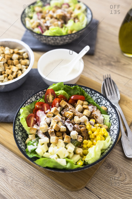 Bowl of Caesar salad with meat- corn and tomatoes