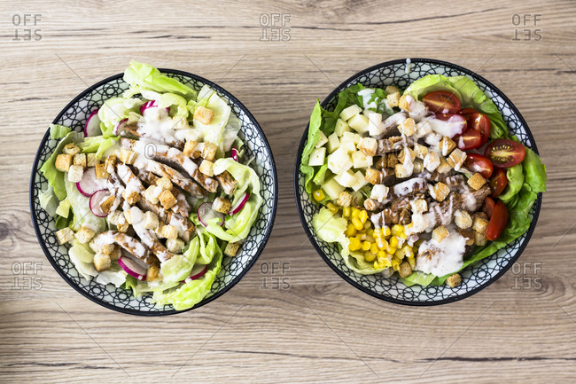 Two bowls of various Caesar salads with meat