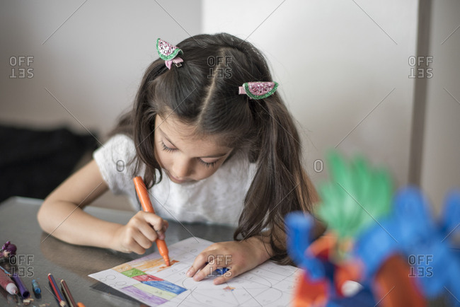 Girl drawing image on paper with a felt pen