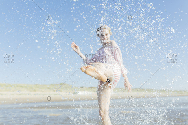 Netherlands- young woman splashing water at the beach in summer