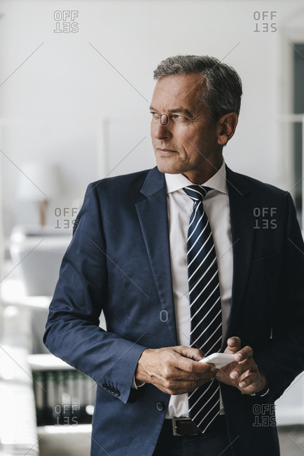 Portrait of mature businessman with cell phone