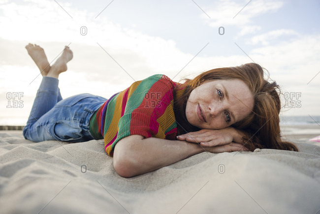 Redheaded woman lying in sand on the beach
