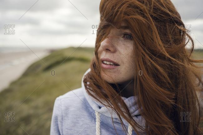 Redheaded woman enjoying fresh air at the beach
